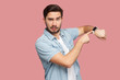 Time is out. Portrait of serious handsome bearded young man in blue casual style shirt standing and looking at camera, pointing on his smart watch. indoor studio shot, isolated on pink background.