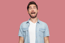 Portrait Of Funny Crazy Handsome Bearded Young Man In Blue Casual Style Shirt Standing With Big Eyes, Tongue Out And Looking At Camera. Indoor Studio Shot, Isolated On Pink Background.