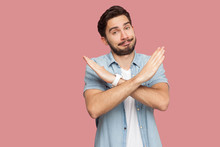 Portrait Of Serious Handsome Bearded Young Man In Blue Casual Style Shirt Standing With X Sign Hands And Looking At Camera. Indoor Studio Shot, Isolated On Pink Background.