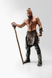 canvas print picture Serious long hair and muscular male model in leather viking's costume with the big mace cosplaying isolated on white studio background. Full-length portrait. Fantasy warrior, antique battle concept.