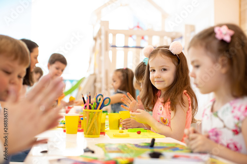 kindergarten children doing arts and crafts with teacher in day care centre - 268836577
