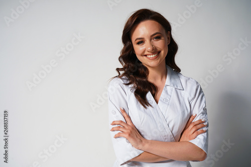 Portrait of beautiful young female doctor in white medical jacket isolated on white background Wallpaper Mural