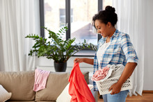 Housework, Laundry And Housekeeping Concept - Happy African American Woman With Basket Picking Dirty Clothes And Cleaning Home