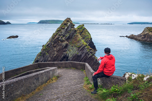 Photo Tourist watching giant cliffs and irish islands at the Dunquin Pier, Dingle Peni