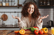 Photo of pretty caucasian woman smiling while cooking salad with fresh vegetables at home