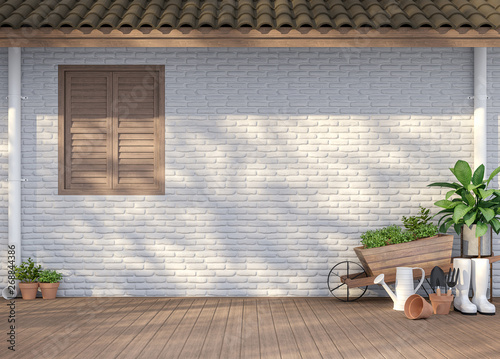 Fotografia House terrace with garden equipment 3d render,There are empty white  brick wall, wood floor and brown roof,Sunlight shining to the wall with tree shadow