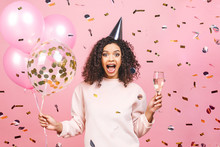Celebration Birthday Concept - Close Up Portrait Of Happy Cheerful Young Beautiful African American Woman With Pink T-shirt With Colorful Party Balloons And Confetti, Champagne.