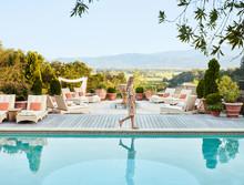 Woman Walking By Pool At Luxury Resort