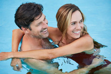 Happy Couple Relaxing In A Swimming Pool