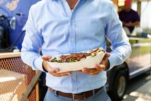 Food Truck: Customer Holds Bacon Cheese Steak Sandwich