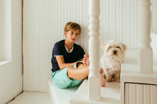 Boy And His Dog Sitting On Stairs At Home