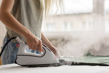 Crop Woman Steaming Clothes While Ironing