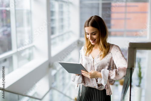 Valokuva  Attractive businesswoman using a digital tablet while standing on the stairs in