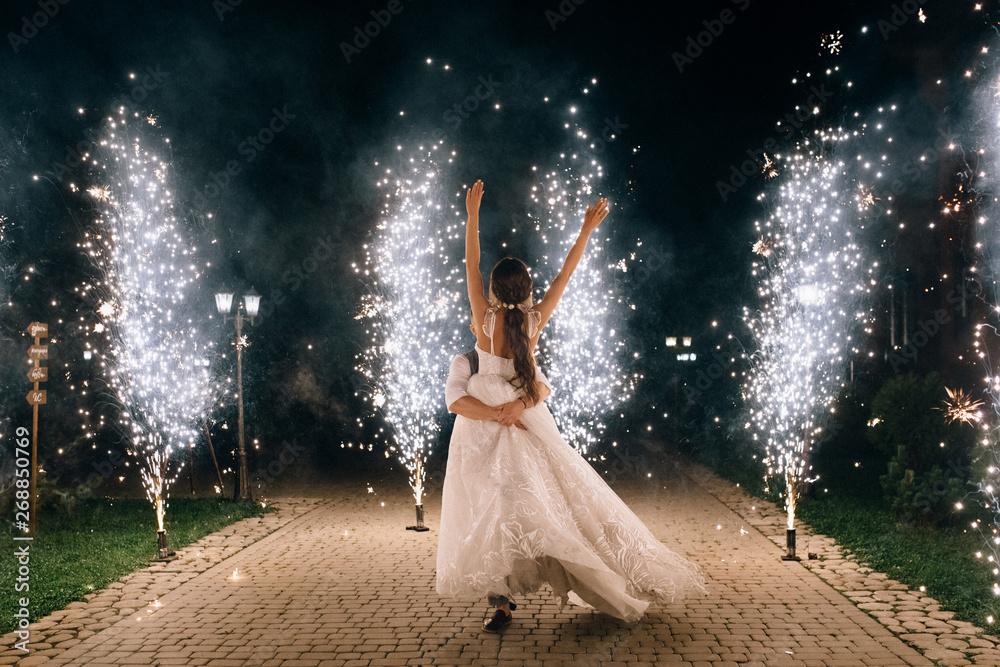 Fototapeta beautiful happy young wedding couple dancing outdoor between fireworks