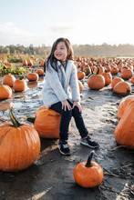 Asian Girl Sitting On A Pumpkin During Fall Season