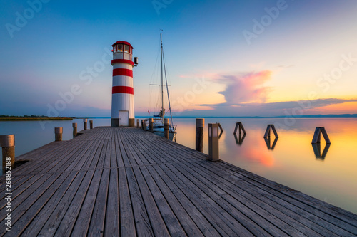 Montage in der Fensternische Leuchtturm Lighthouse at Lake Neusiedl, Podersdorf am See, Burgenland, Austria. Lighthouse at sunset in Austria. Wooden pier with lighthouse in Podersdorf on lake Neusiedl in Austria.