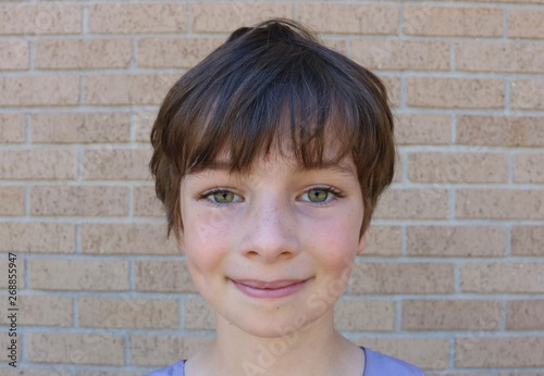 Valokuvatapetti Face of young child with stunning hazel eyes, short brown pixie hair and dimples