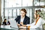 Young man and woman having a business conversation while sitting with laptop at the bar or modern spacious office - 268860548