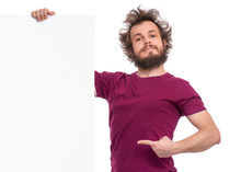 Crazy Bearded Man With Funny Haircut Showing Empty Blank Signboard With Copy Space. Proud Guy Peeking Out From Behind Big White Banner, Isolated On White Background.