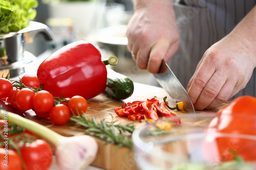 Deurstickers Hot chili peppers Professional Culinary Man Cutting Hot Chili Pepper. Man Chopping Yellow Ingredient to Small Pieces on Wooden Board for Tasty Salad. Healthy Dieting Recipe. Organic Food Horizontal Photography
