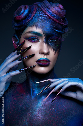 Beautiful girl with art fashion make up, creative hairstyle, long nails. Design manicure. Beauty face.