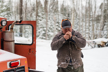 Older Man Operating Vintage Machine In Snow Field Stops For A Smoke Cigarette