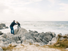 Father And Son Climbing Rocks Holding Hands