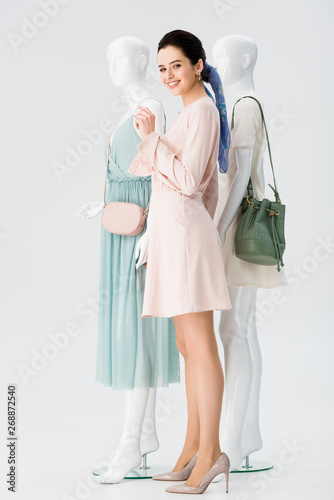 beautiful smiling girl posing with mannequins in dresses isolated on grey Wall mural