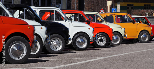 A row of colorful vintage Fiat 500 s  in a roadside parking lot on a sunny day.