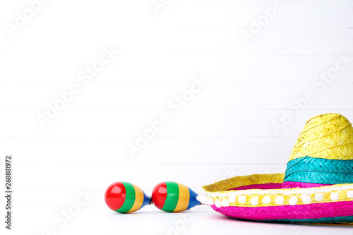 Mexican hat and maracas on white background