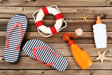 Sunscreen Bottles With Seashells, Lifebuoy And Flip Flops On Brown Wooden Table