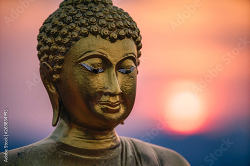 Buddhist Statue Photographed with the Red Sunset in the Background