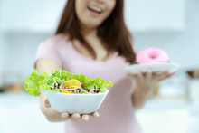 Young Beautiful Woman Take Care Her Health By Eating Salad And Fruit Instead Of Eating Fat And Calories