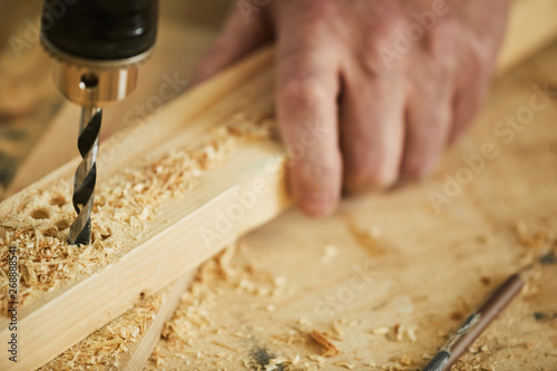 Obraz Extreme closeup of unrecognizable carpenter drilling wood while working in joinery, copy space - fototapety do salonu