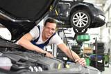 Portrait fröhlicher Automechaniker in der Werkstatt - Beruf Monteur Reparatur Fahrzeuge // car mechanic in a workshop - engine repair and diagnosis on a vehicle - 268892582