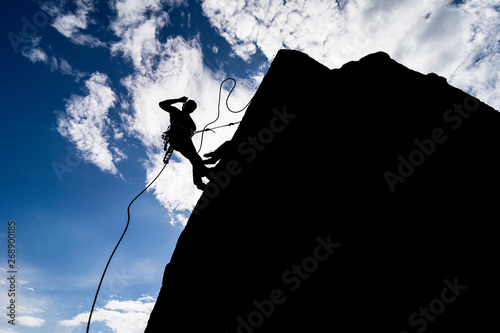 Photo A dramatic silhouette of a climber rappeling down a rock wall