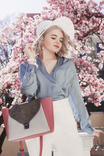 Outdoor Fashion Portrait Of Young Beautiful Elegant Lady Wearing  Stylish White Hat, Pearl Earrings, Blue Silk Blouse, Trousers, Holding Trendy Handbag, Posing In Street With Blooming Magnolia Tree.