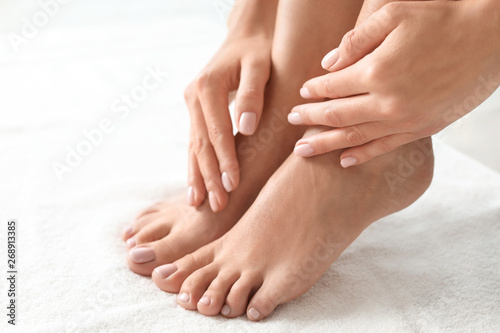 Poster Pedicure Woman with beautiful feet on white towel, closeup. Spa treatment
