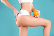 Leinwandbild Motiv Closeup view of slim woman in underwear with orange on color background. Cellulite problem concept
