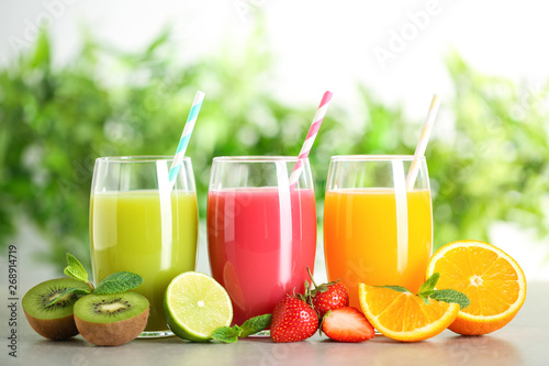 Foto auf Gartenposter Saft Glasses of different juices with straws and fresh fruits on table against blurred background