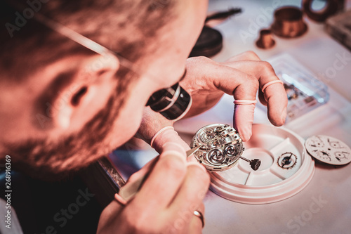 Photo Mature clockmaster is fixing old watch for a customer at his busy repairing workshop