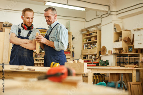 Photographie  Waist up portrait of senior carpenter teaching apprentice  while working  in joi