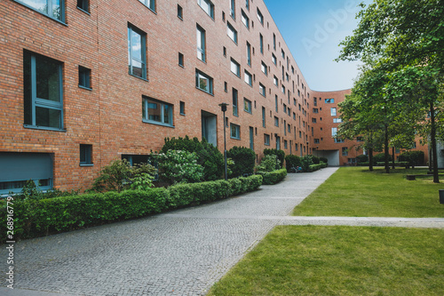 Leinwand Poster residential building exterior with park and meadow - apartment house