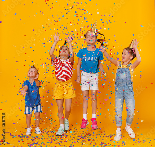 obraz dibond happy children on holidays jumping in multicolored confetti on yellow