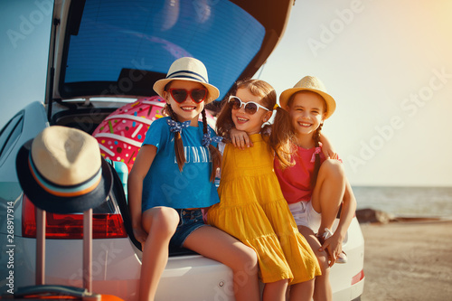 happy children girls friends sisters on the car ride to summer trip. - 268917914