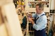 Side view portrait of senior carpenter choosing screws in workshop, copy space