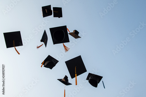 Throw a black hat of graduates in the sky. Fototapeta