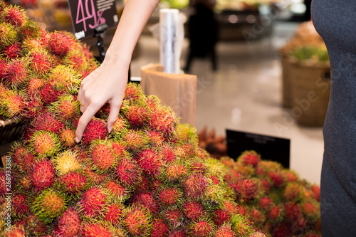 Hand of adult Asian Woman in gray dress select pick up Rambutan