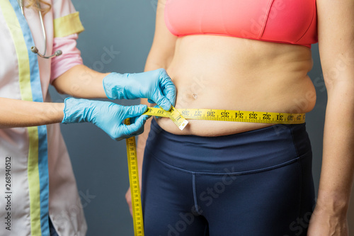 Doctor taking obese patient's body fat measurements Wallpaper Mural