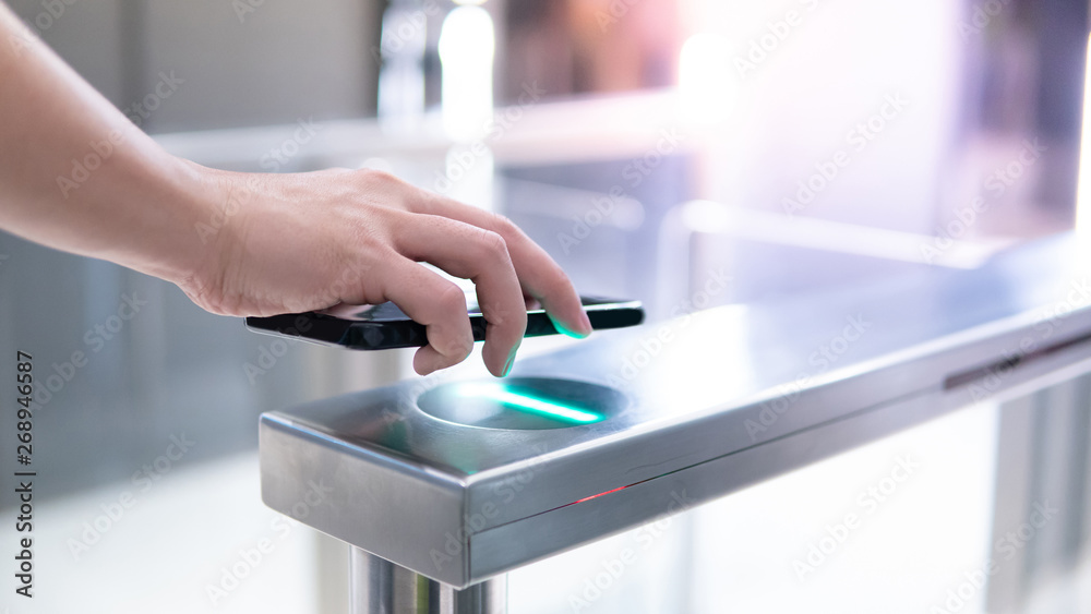 Fototapeta Male hand using smartphone to open automatic gate machine in office building